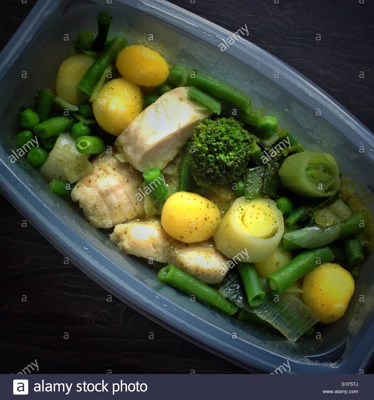 Microwave meal of fish and vegetables in plastic tray from above - Stock Image