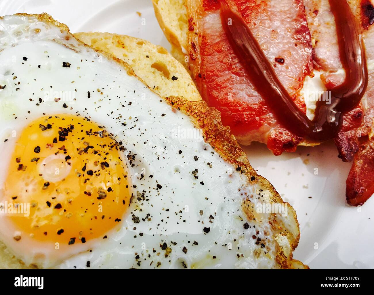 Fried egg and bacon roll with brown sauce Stock Photo