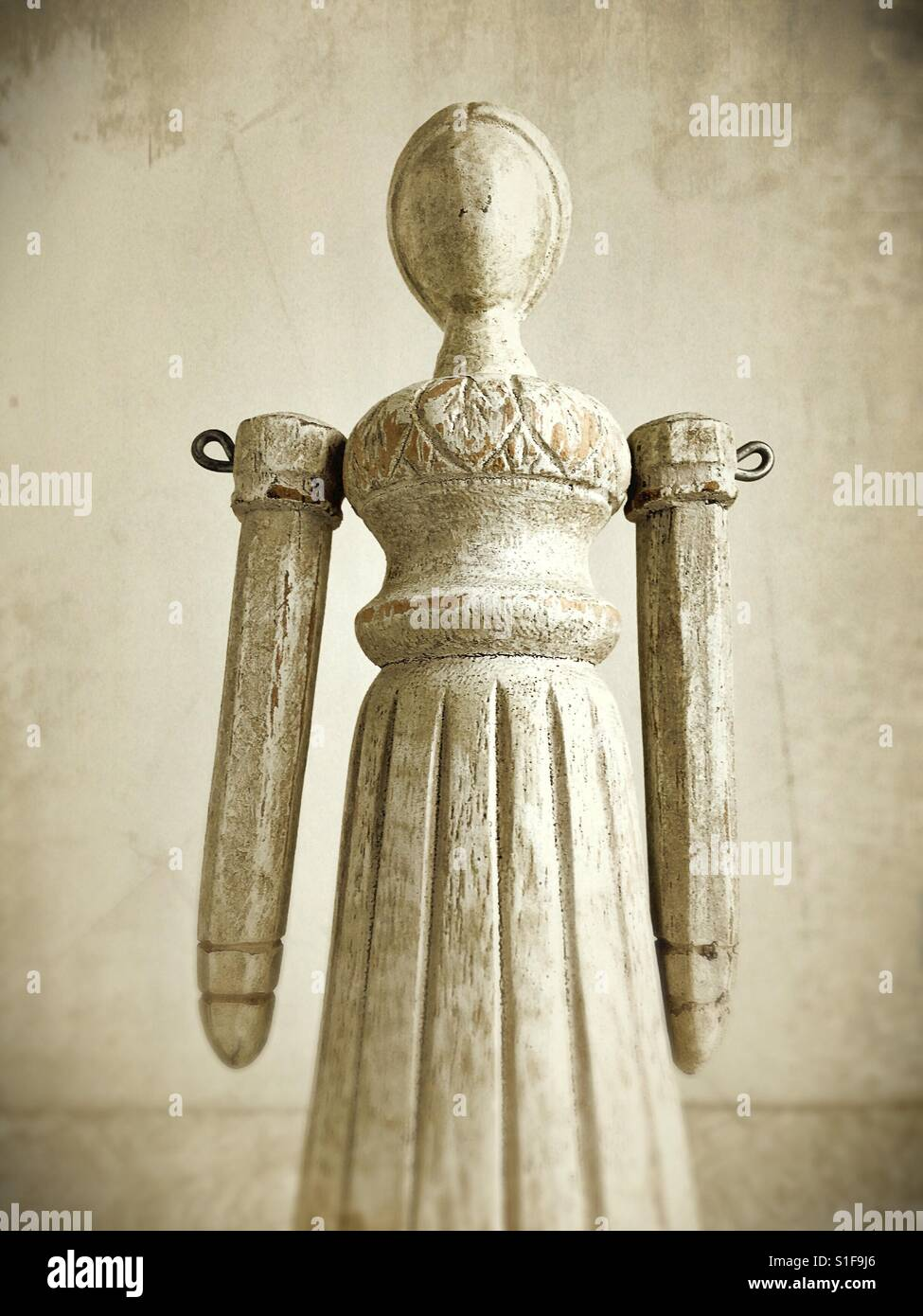 An old fashioned looking female wooden figure. - Stock Image