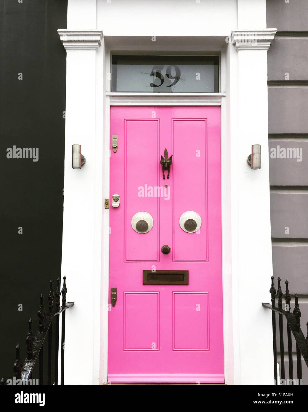 Pink door with eyes - funny face - Stock Image