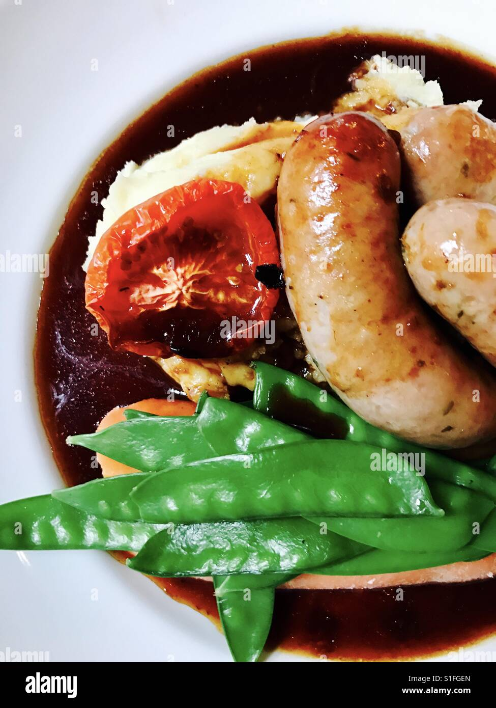 Sausage and mash with greens and tomato Stock Photo