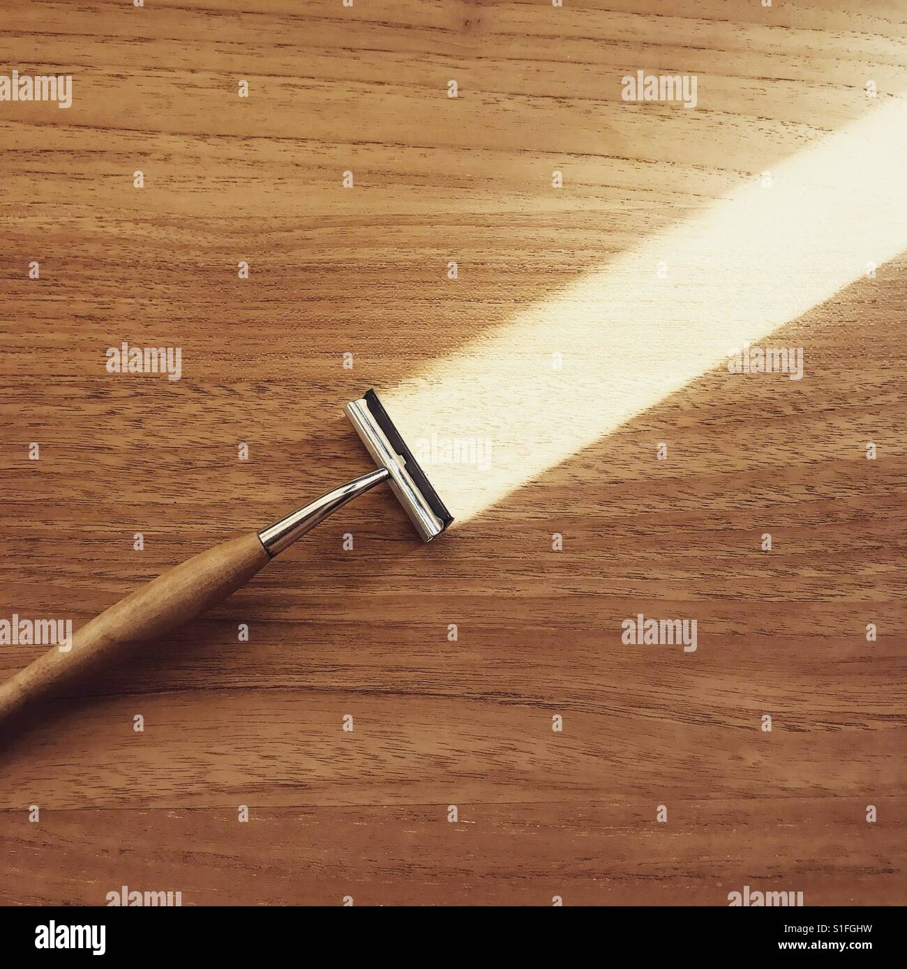 A razor looks like it shaves wood by being lit from a certain angle - Stock Image
