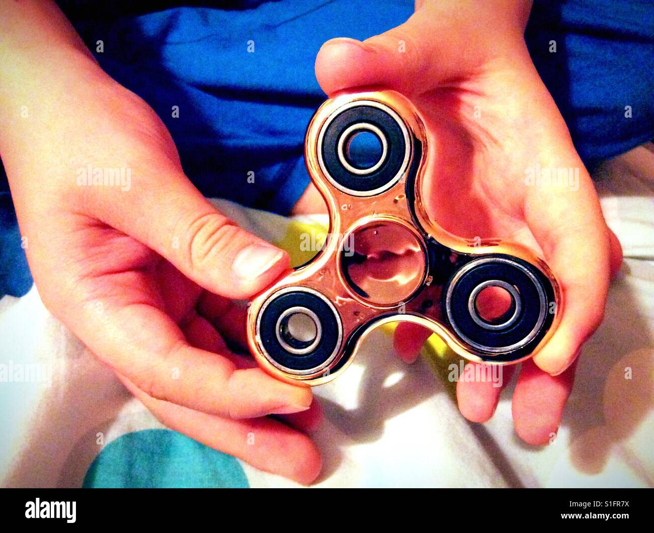 A child's hands holding a gold coloured fidget spinner. - Stock Image