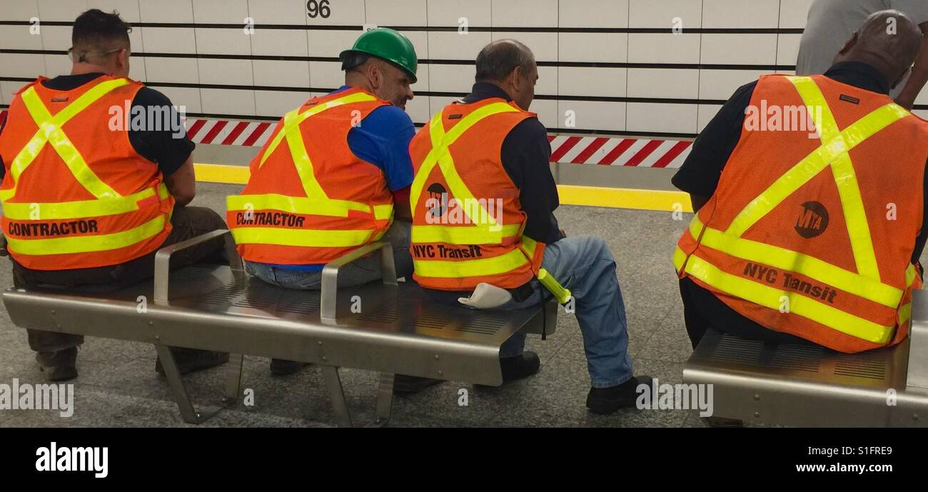 Contractors at Lunch with hard hats, flourescent bibs - Stock Image