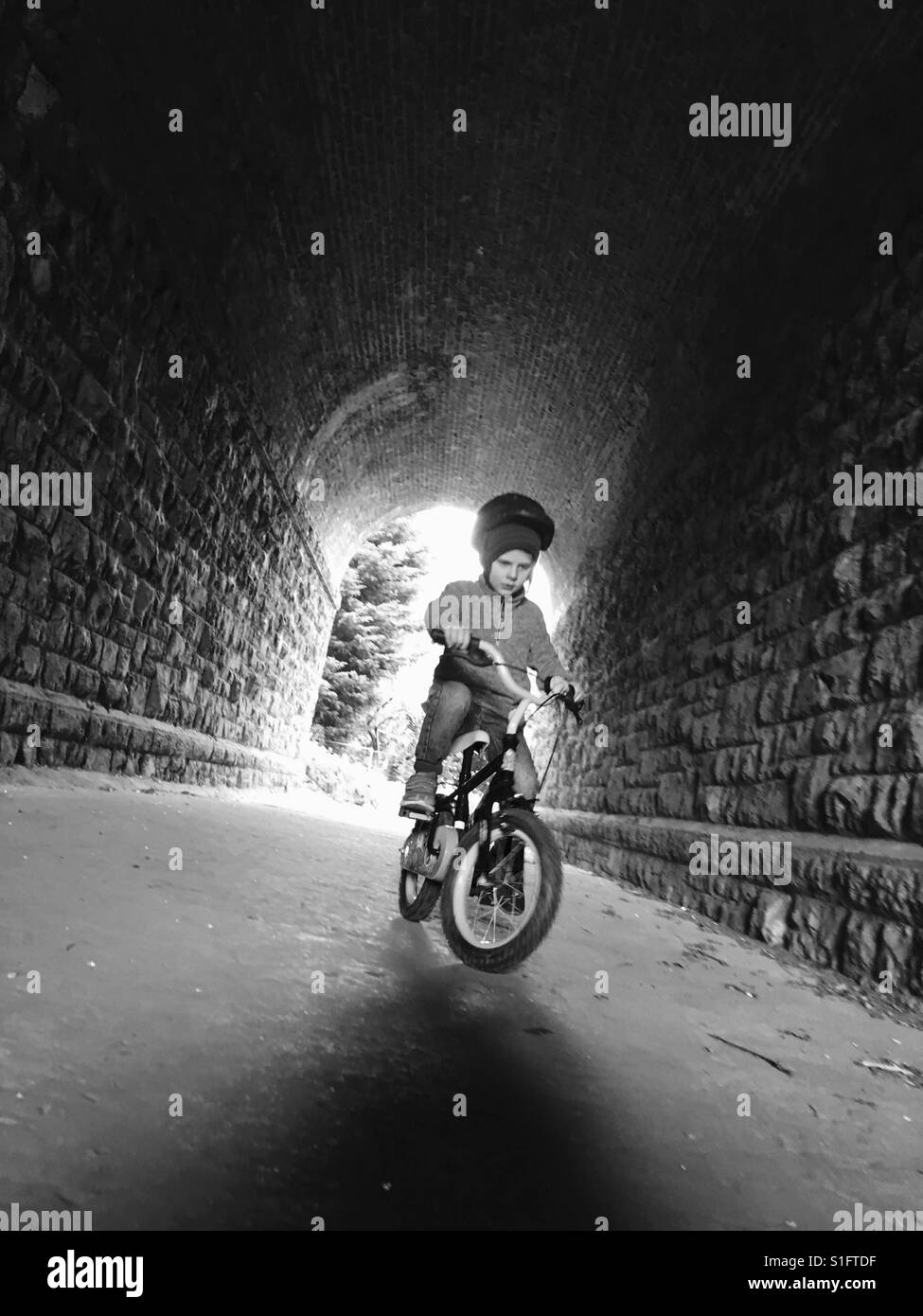 Boy riding a bicycle through tunnel - Stock Image