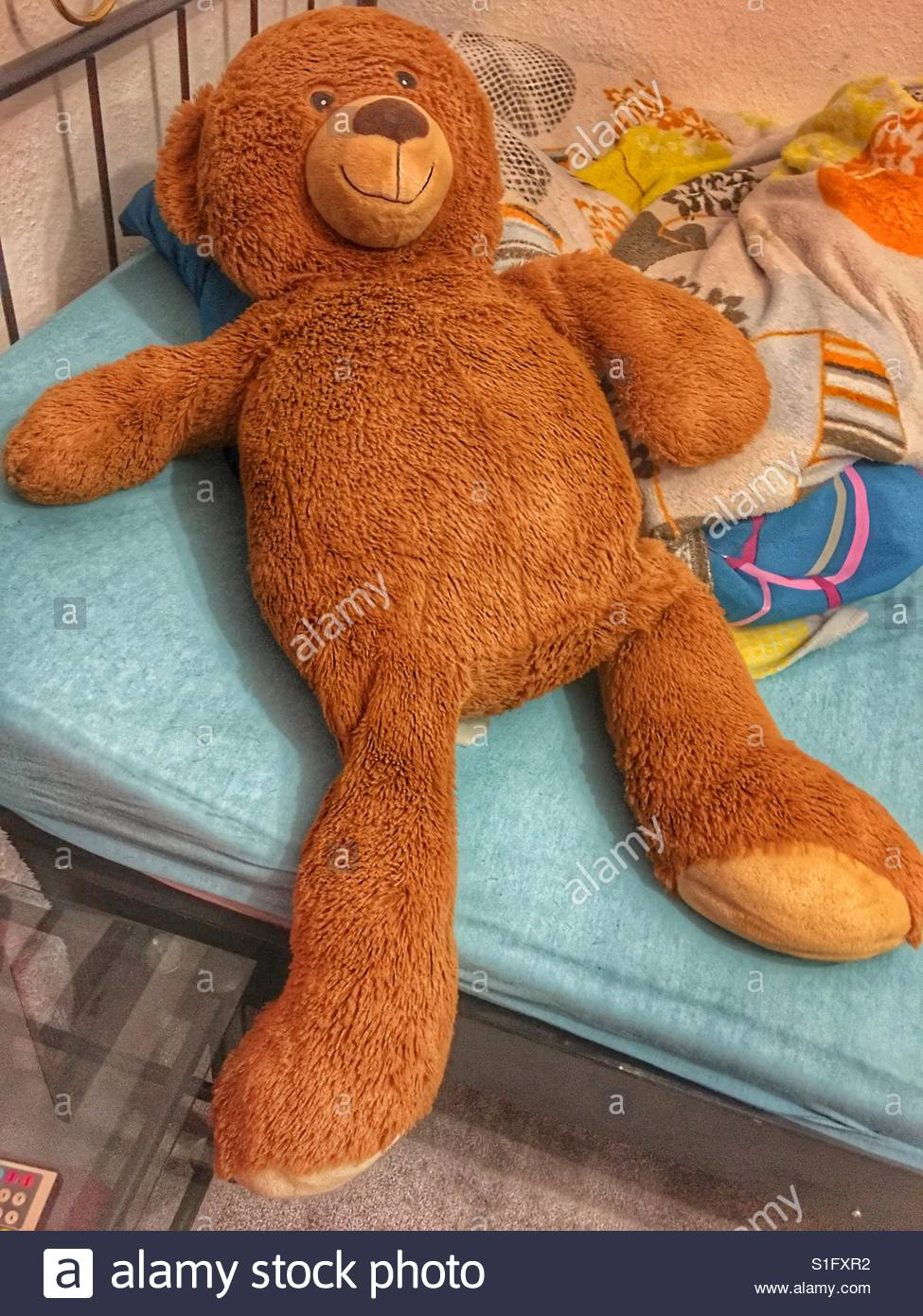 Very big teddy bear on a messy bed - Stock Image