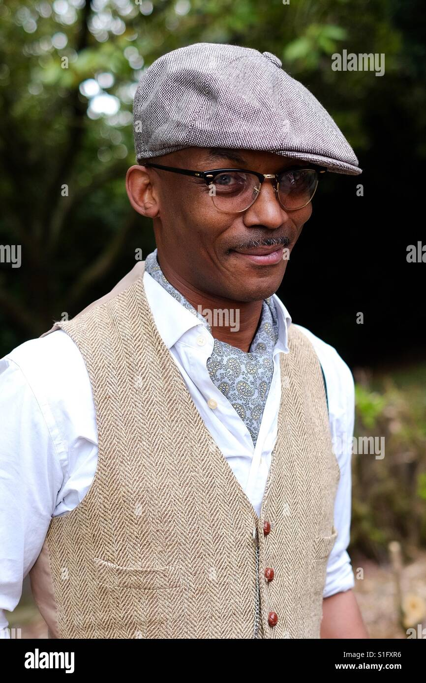 Young black man dressed in vintage clothing with a cravat , flat cap and waistcoat. - Stock Image