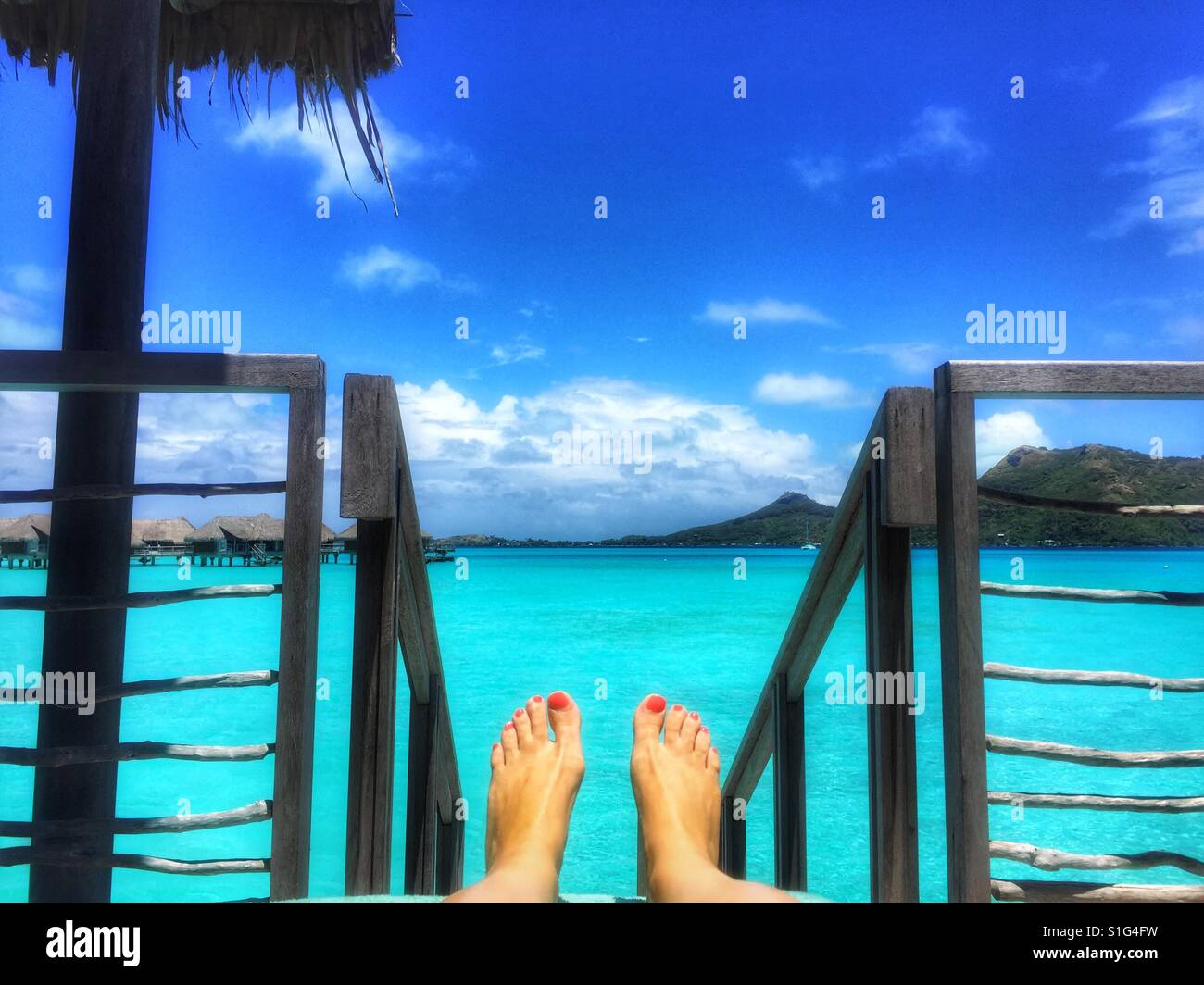Feet with painted toenails on the deck of an overwater bungalow in Bora Bora, South Pacific - Stock Image