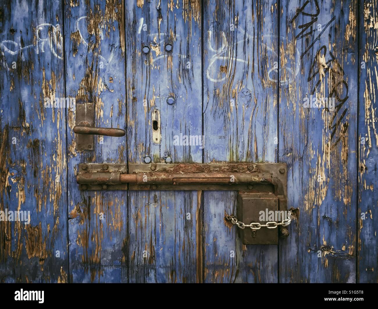 Rusty sliding door lock on weathered wooden blue door - Stock Image