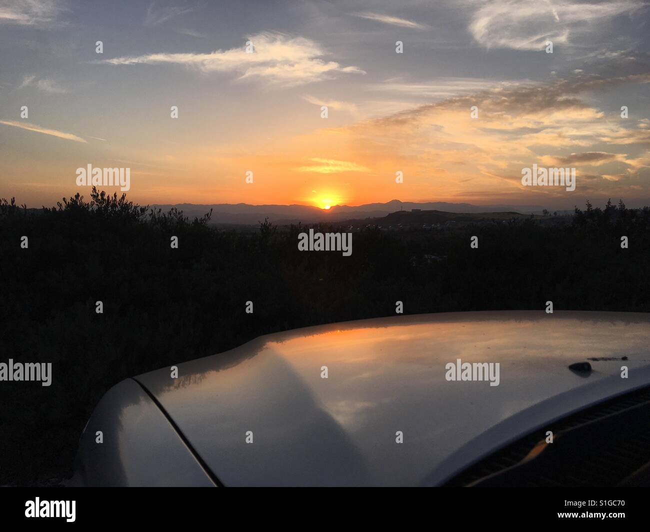 Catching a beautiful sunset while parked at a lookout point. - Stock Image