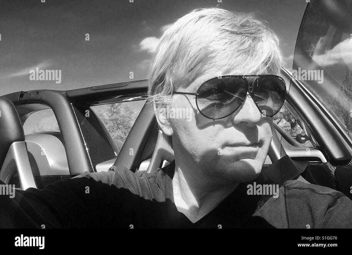 9e24a3d844 Man in Porsche Design sunglasses behind the wheel of a Porsche Carrera GT -  Stock Image