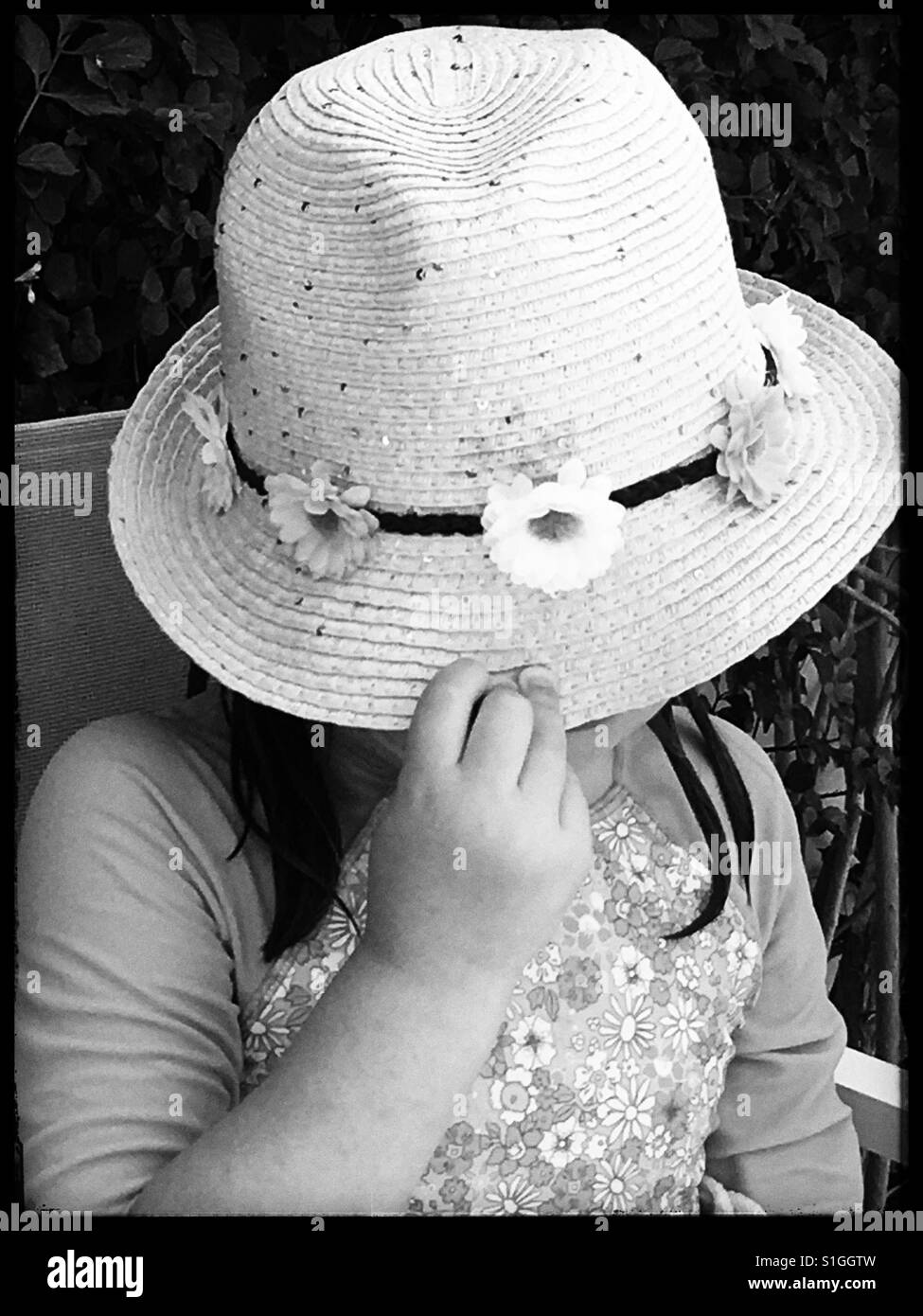 Angry girl covering her face with her sunhat. - Stock Image