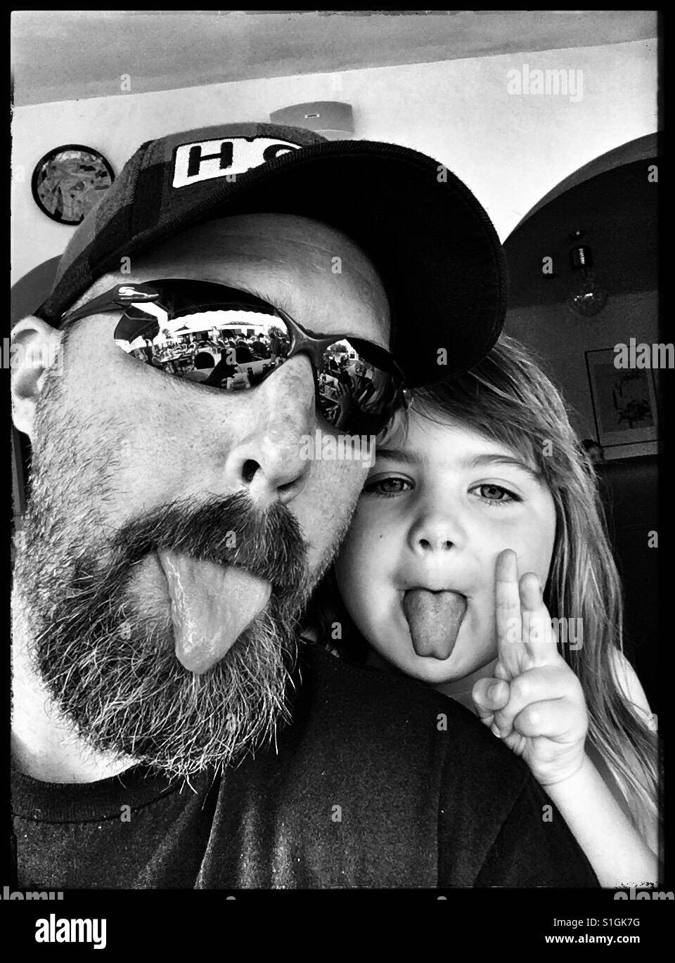 Father and daughter sticking their tongues out. - Stock Image