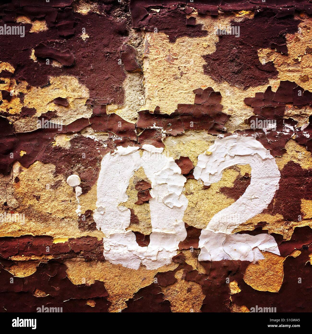 The numbers zero and two painted on a dilapidated brick wall - Stock Image