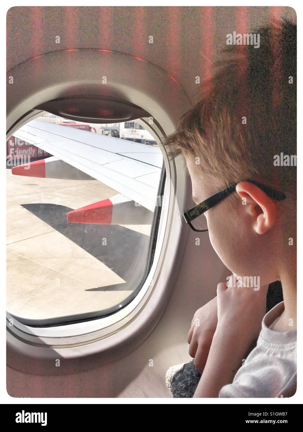 6 year old Boy looking out of Aeroplane window. - Stock Image