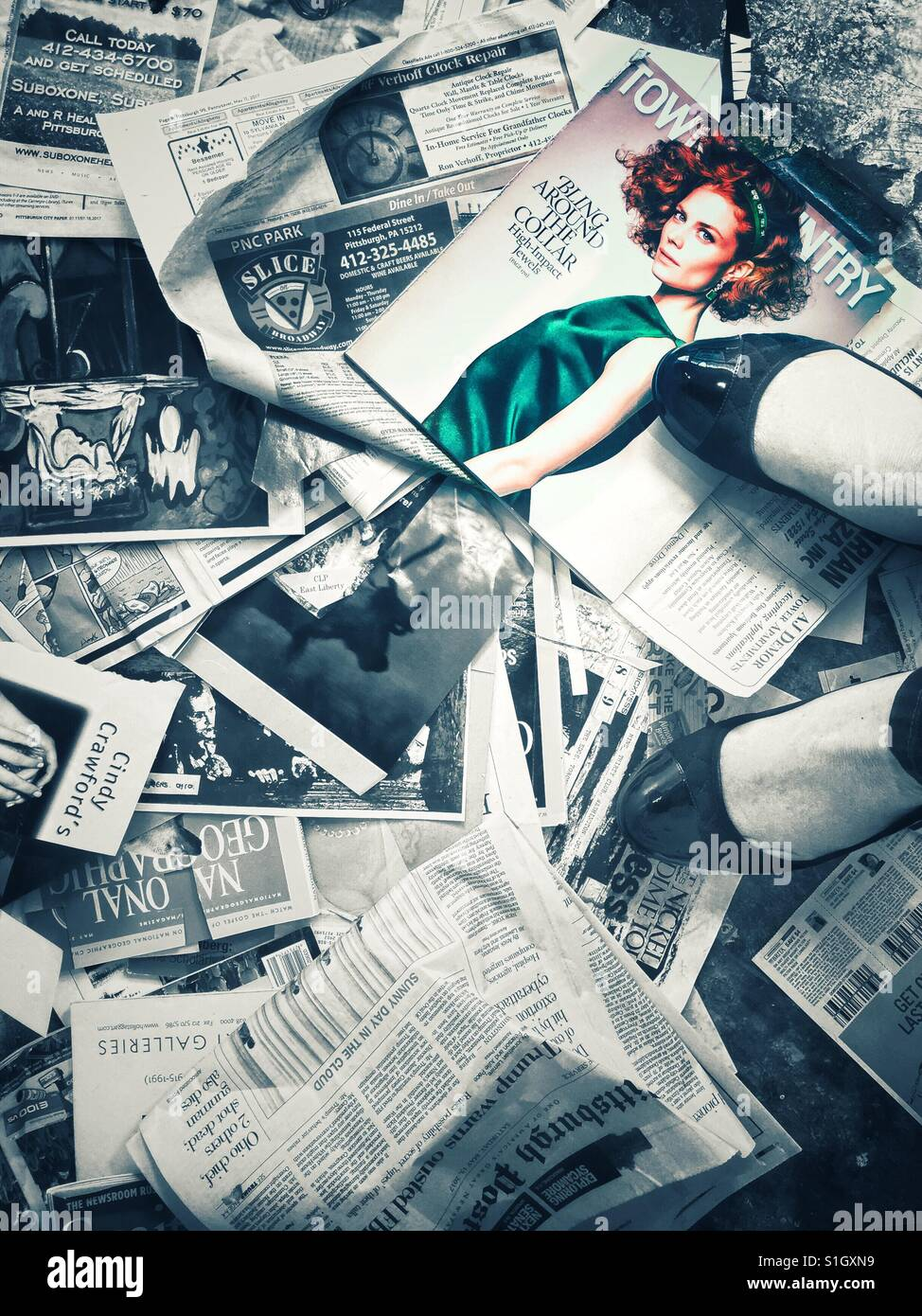A woman's feet standing on a large number of magazine pages and clippings strewn in the floor, with an image - Stock Image