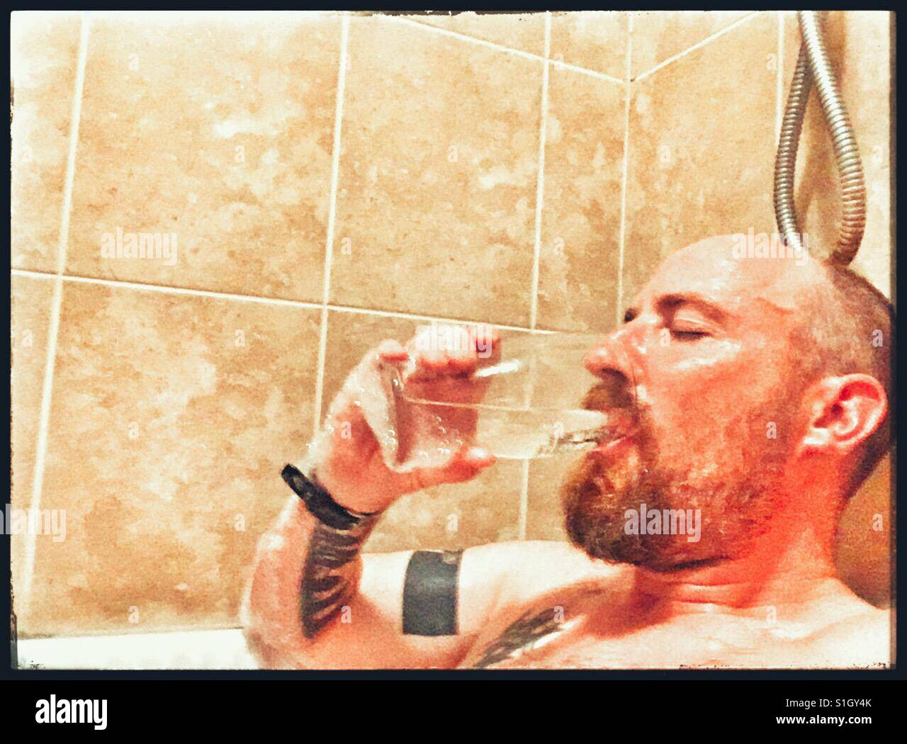 Man drinking a pint of water while immersed in a very hot bath. - Stock Image
