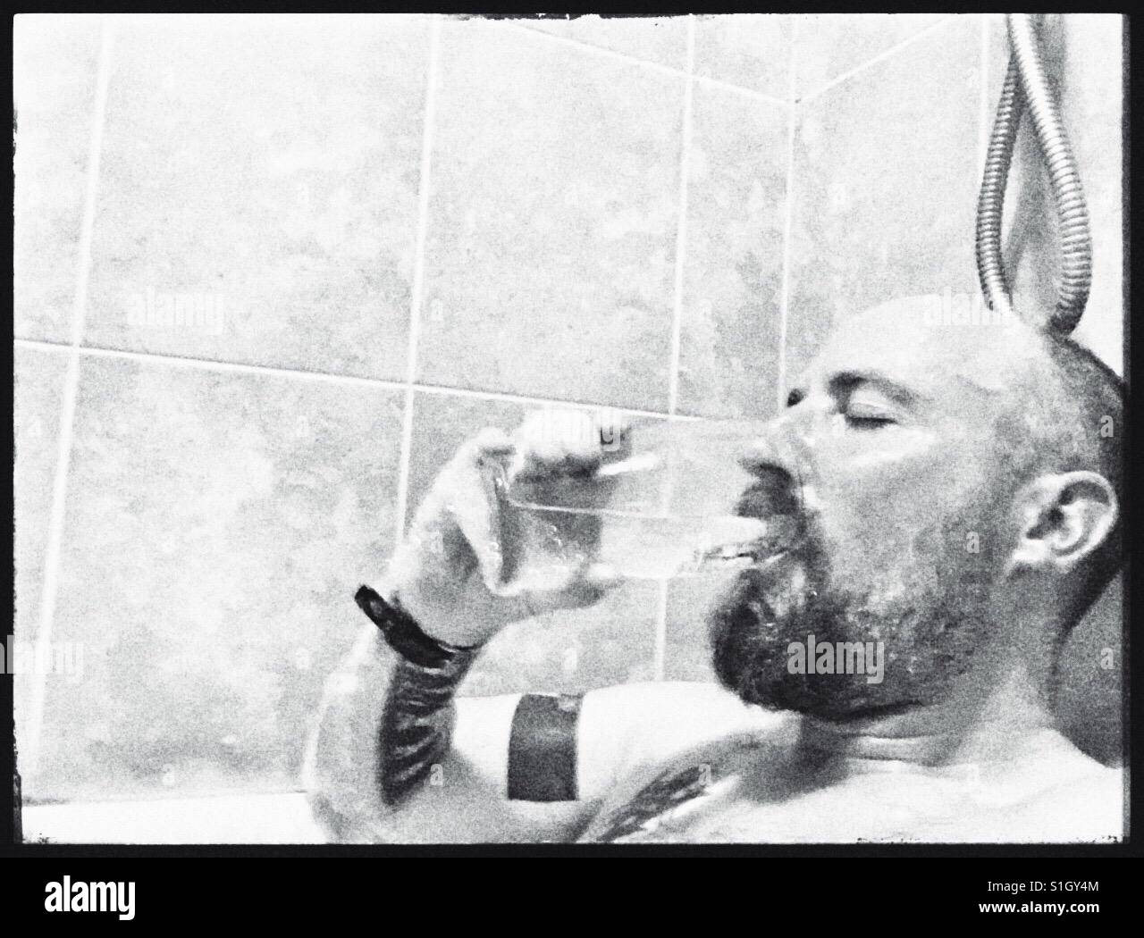 Man drinking a pint of water whilst immersed in a very hot bath. - Stock Image