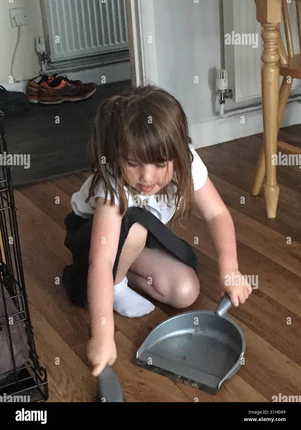 Little girl helping with the housework. - Stock Image