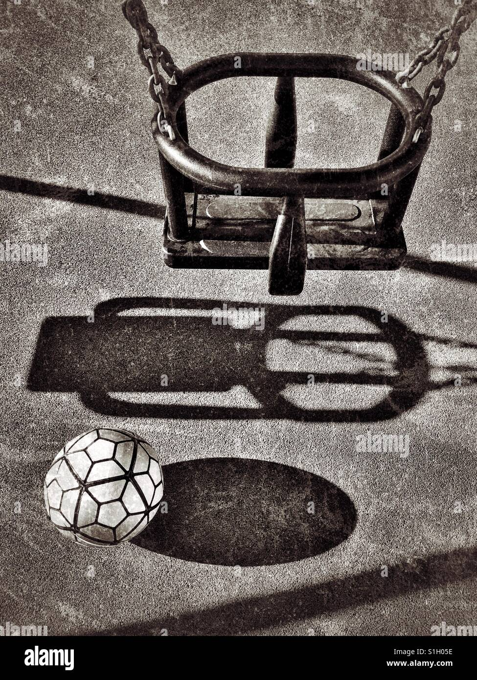 Shadows of a swing and football in a children's playground area. Nobody is present. Where are the children? - Stock Image