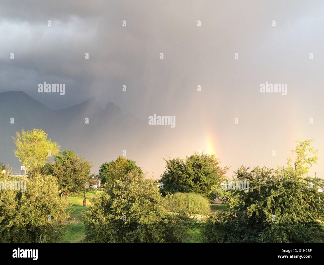 Rainbow in a turmoil of clouds - Stock Image