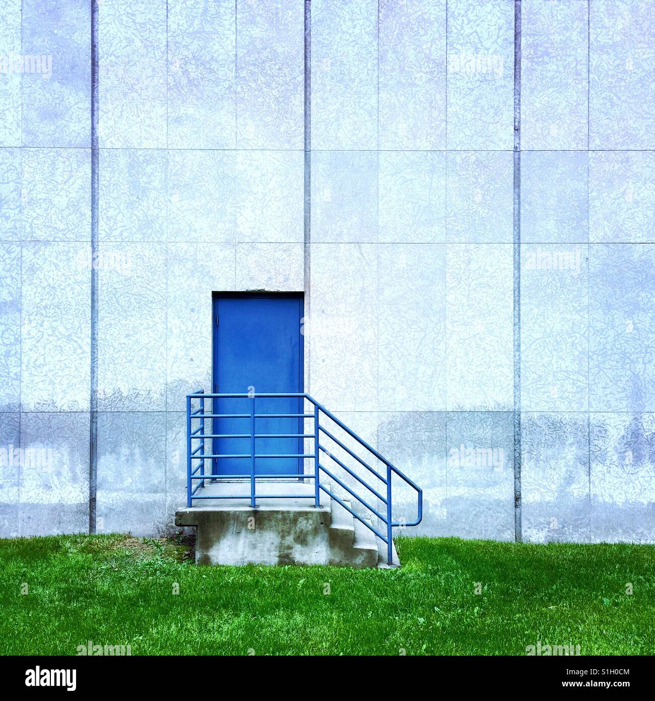 A simple composition of a blue door on the side of the building - Stock Image