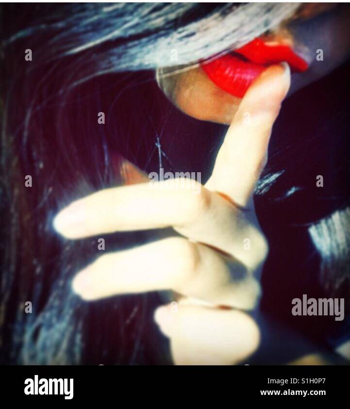 Close up of a young woman holding her finger to her red lips - Stock Image