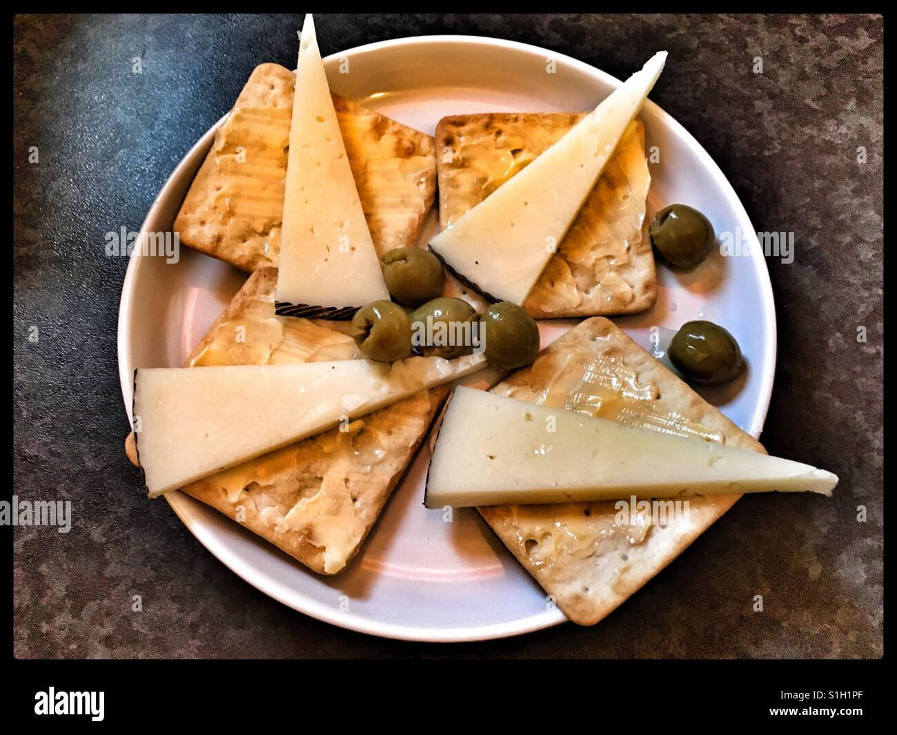 Tapas of Manchego Cheese, olives and cream crackers. - Stock Image