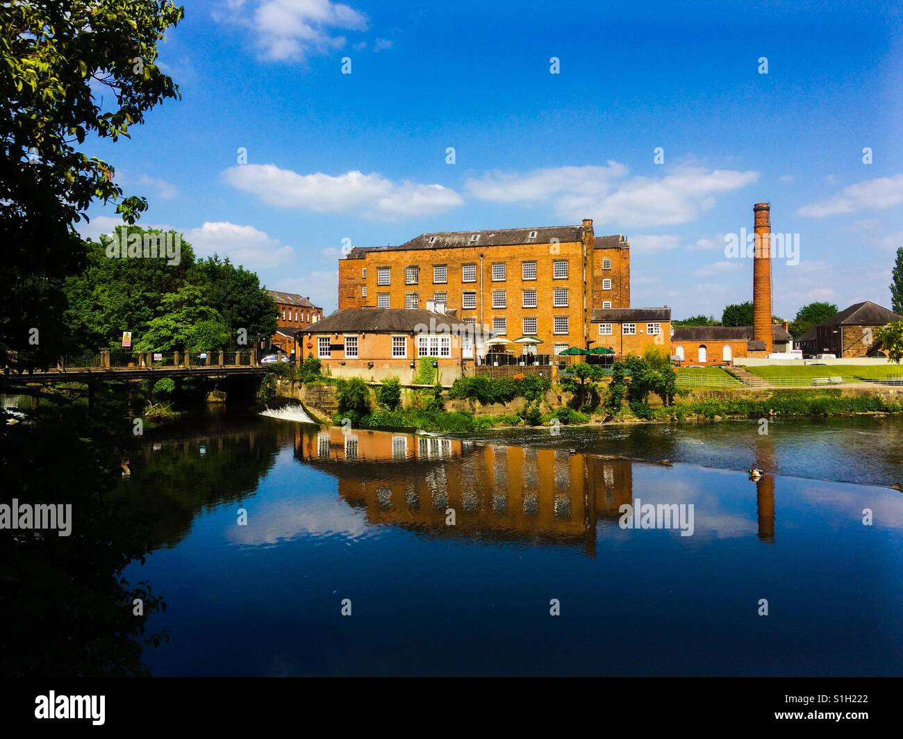 Darley Abbey Mill reflected in the River Derwent Derby England UK - Stock Image
