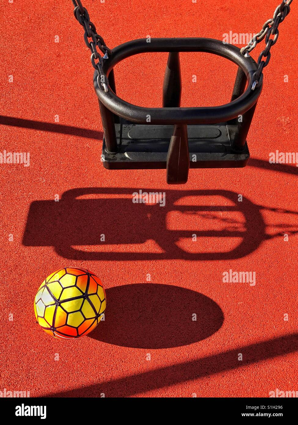 A lone football sits underneath a single swing in a children's playground. It's a bright summers afternoon - Stock Image