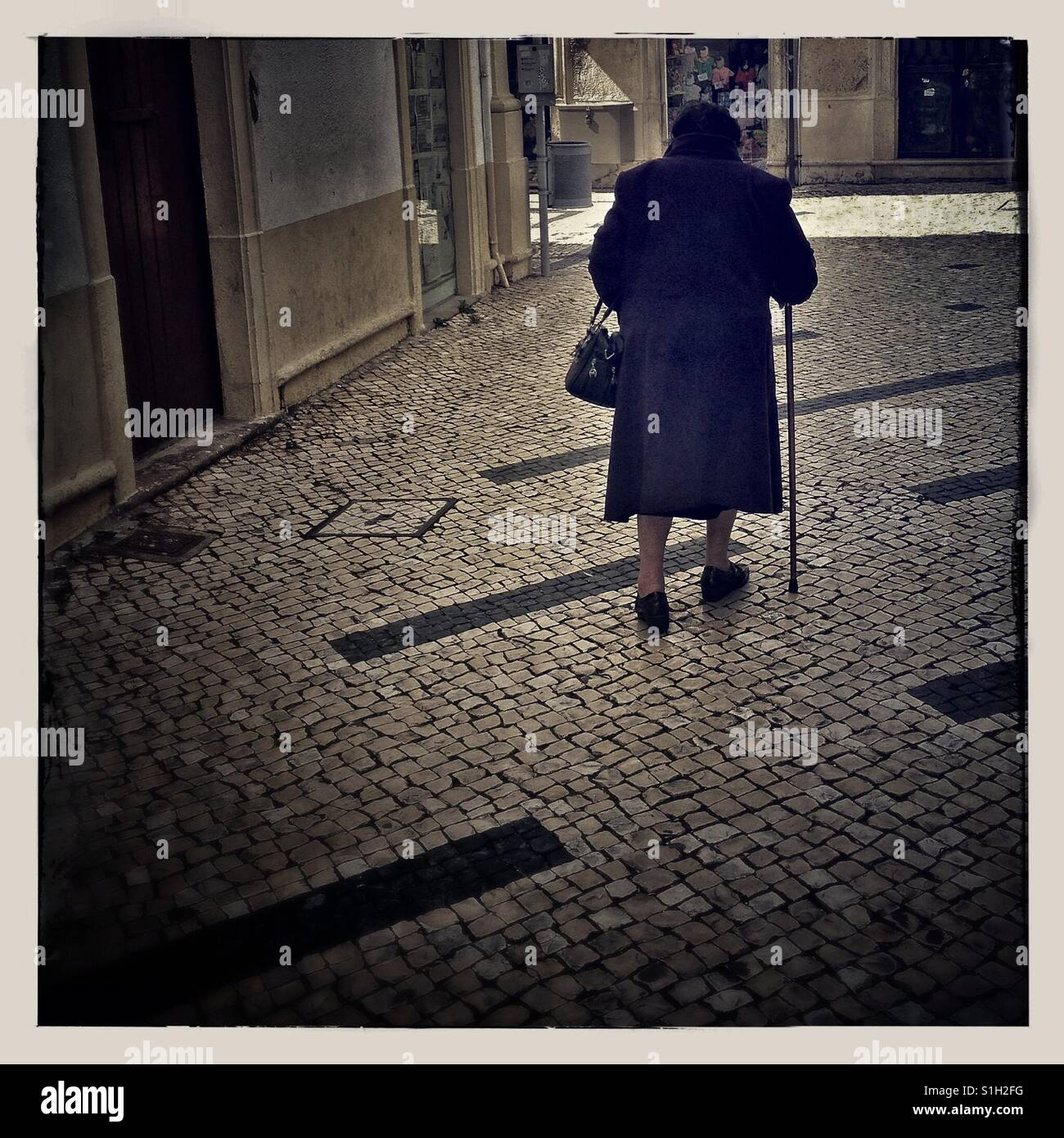 The back view of an old lady walking on the street - Stock Image