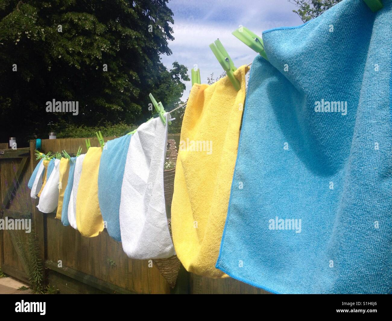 Washing line full of colour. Pegged out in the summer sunshine. - Stock Image