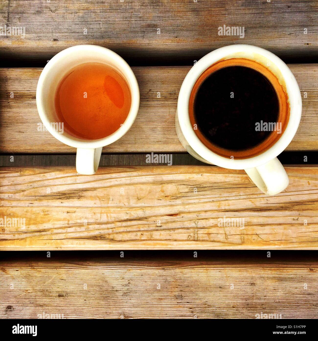An overhead shot of an Americano and a cup of herbal tea on a wooden bench - Stock Image