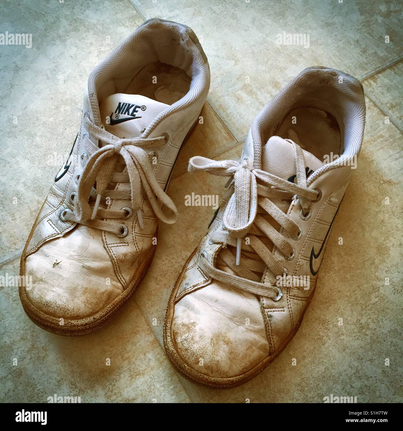 Old dirty worn-out running shoes - Stock Image