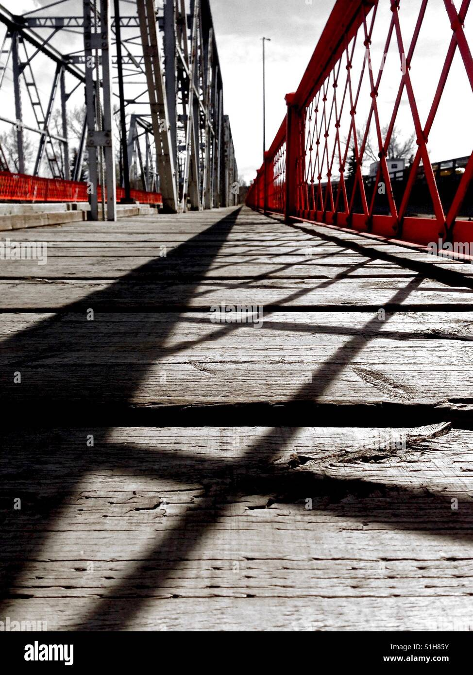 Low view of bridge in monotone and red - Stock Image