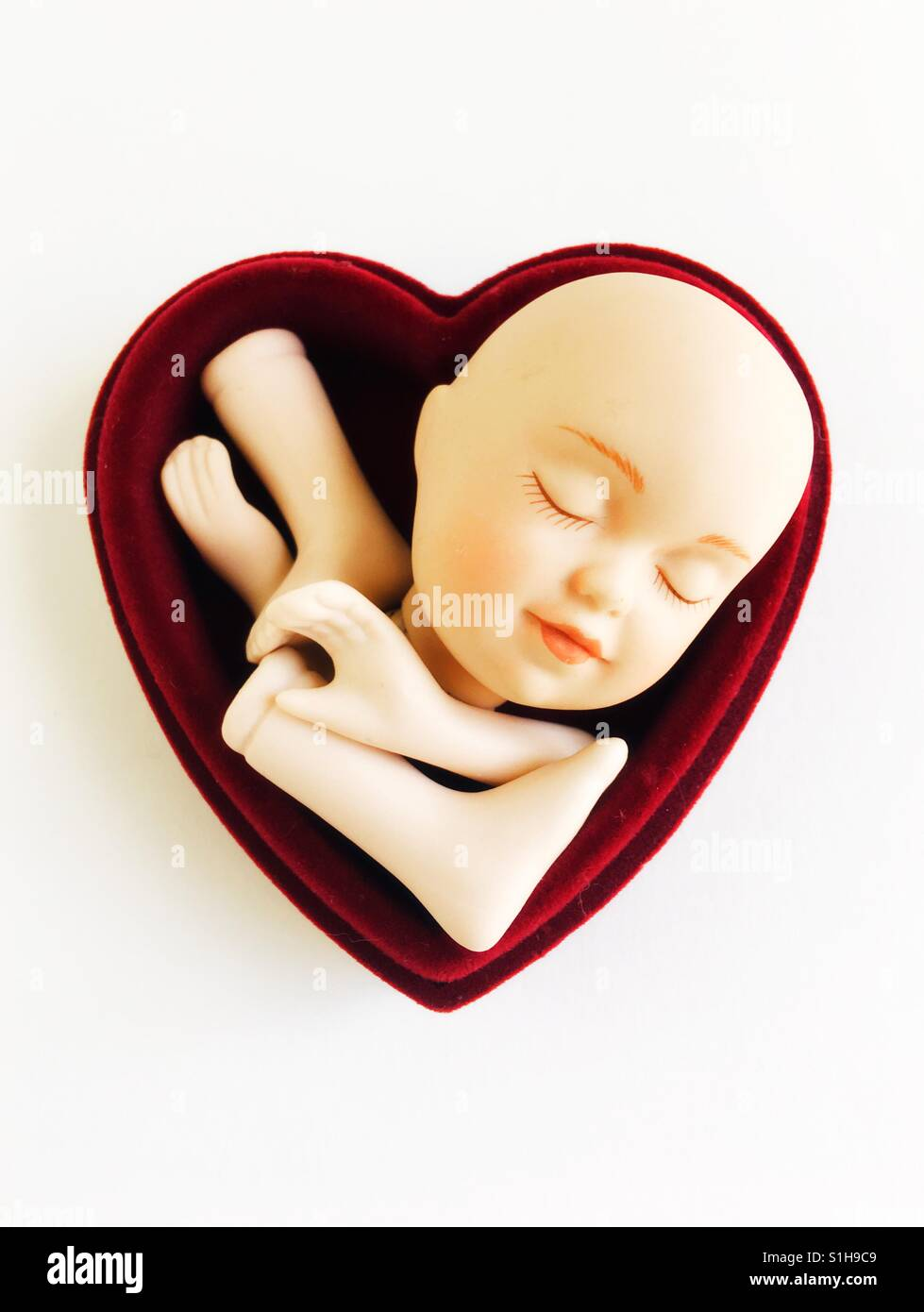 A heart with doll parts. - Stock Image