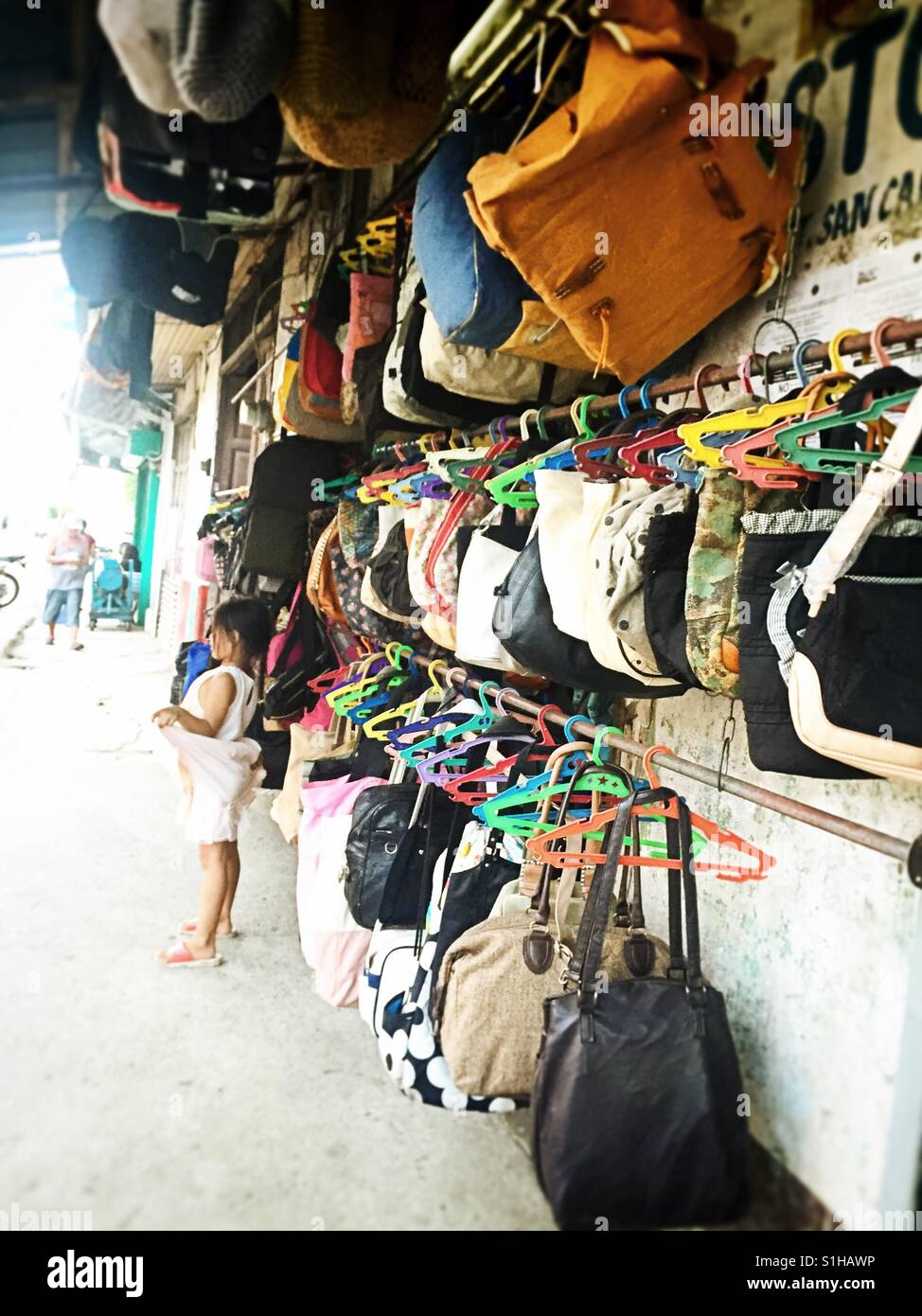 a child playing outside their second hand bags store.  philippines ... 058fe7a1fc