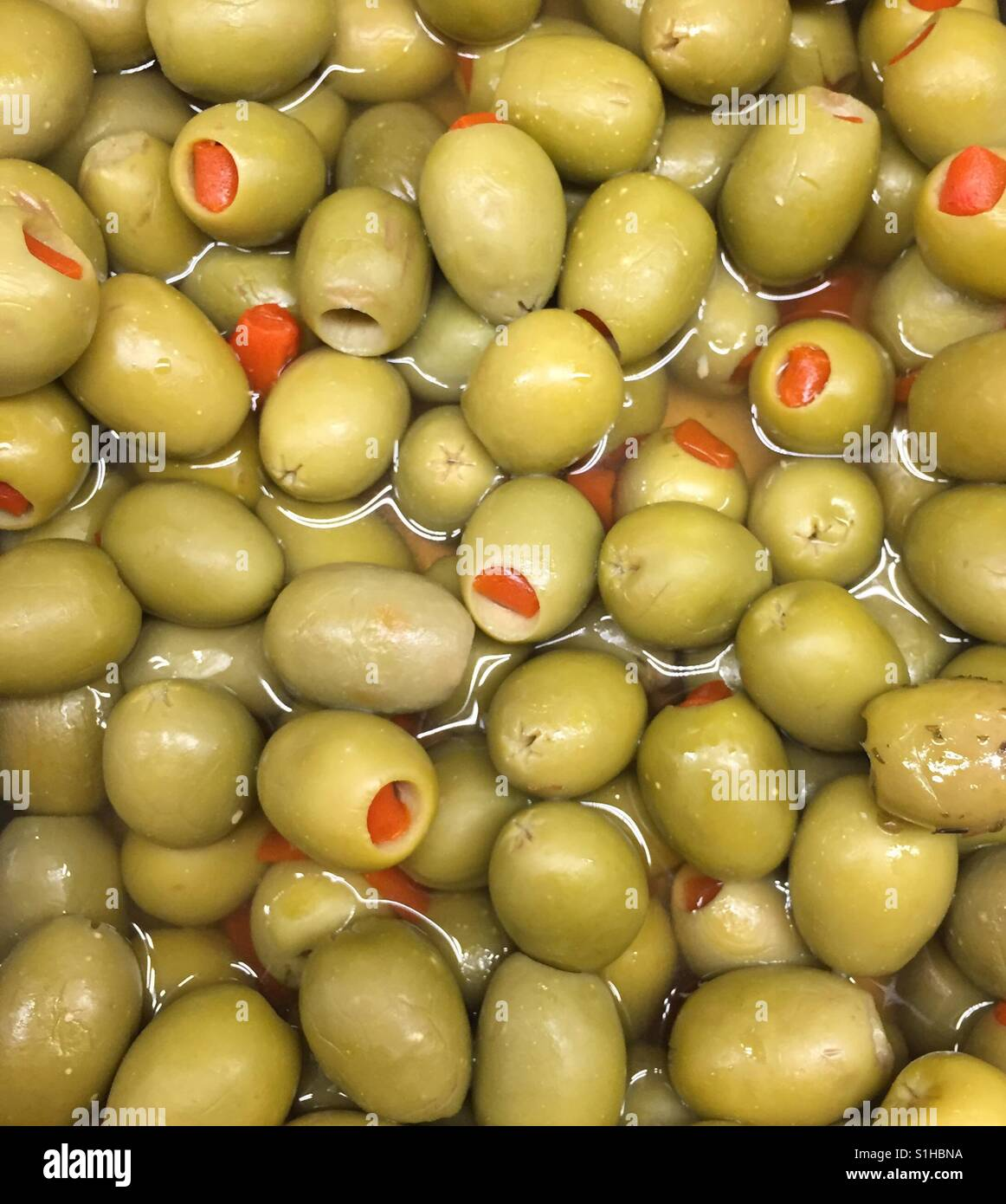 A pool of salty green olives. - Stock Image
