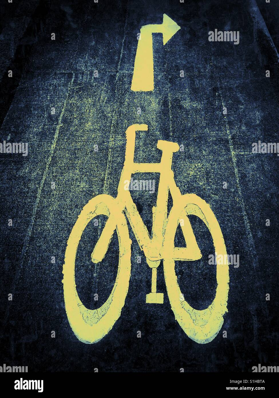 The yellow symbol sign of a bicycle - used to indicate a cycle lane. The arrow pointing right tells cyclists they - Stock Image