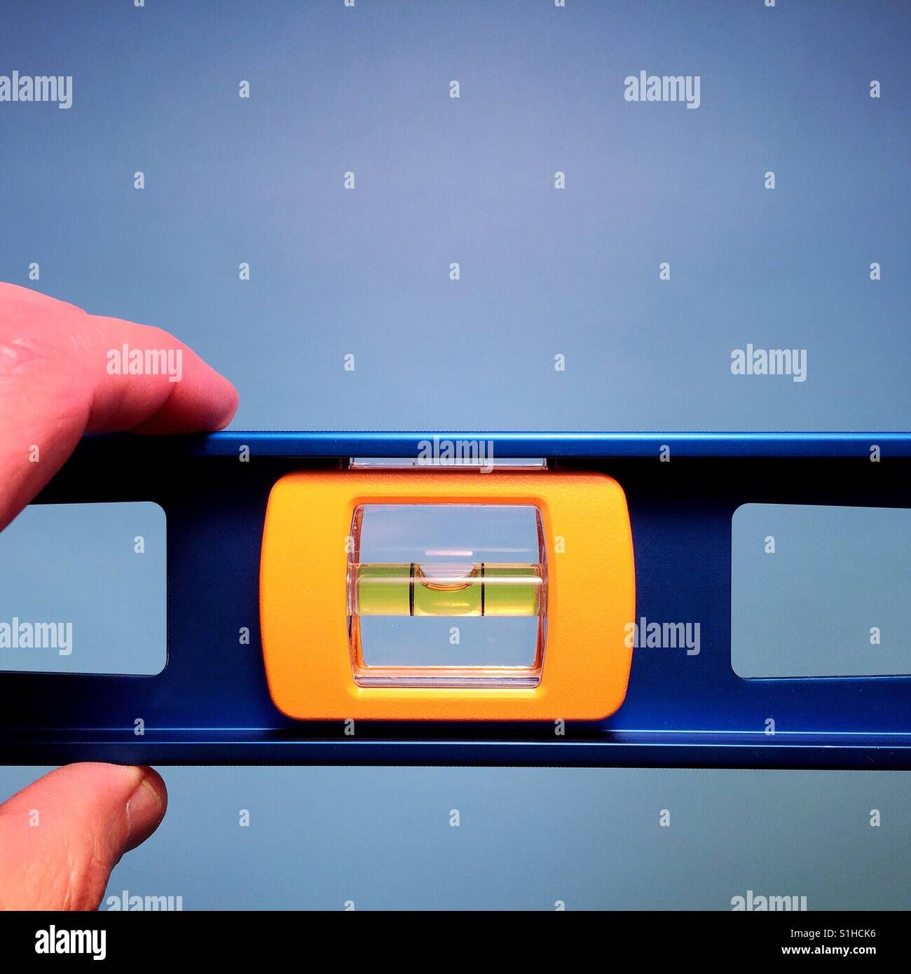 A close-up shot of a man holding a carpenter's level against a blue background - Stock Image