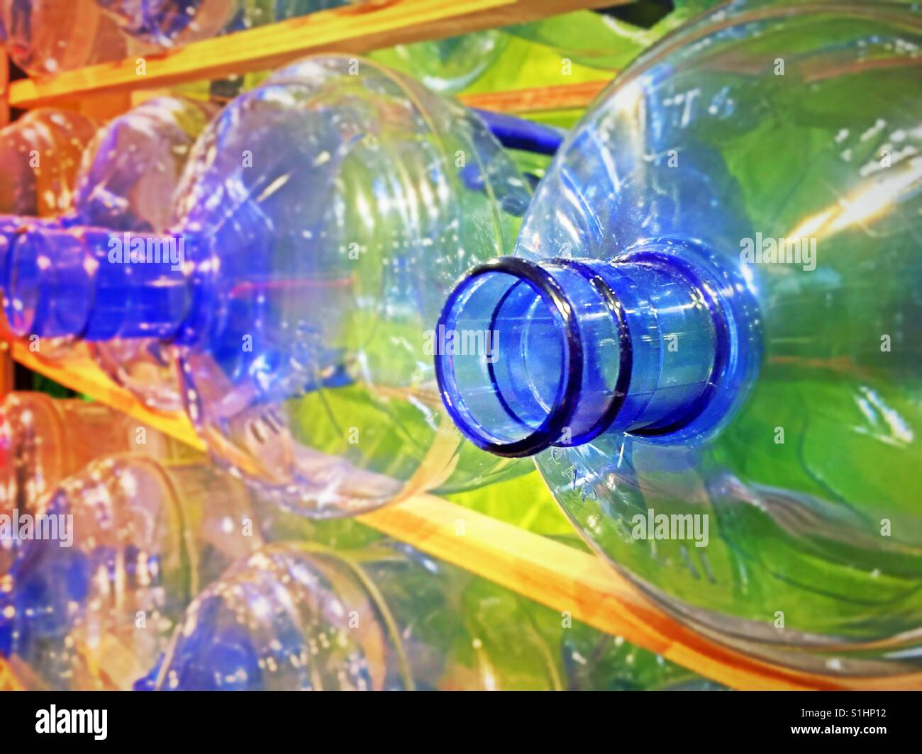 Rack of empty brightly colored plastic water bottles, USA. - Stock Image