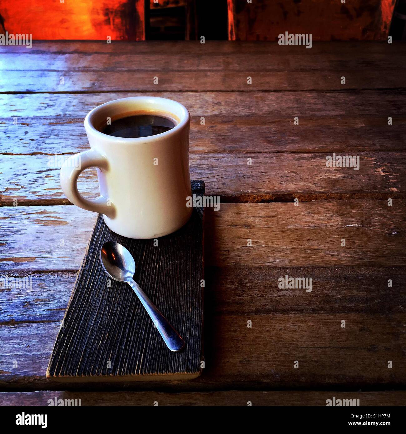 A fresh Americano beverage and a spoon on a wood serving plate on a wooden table - Stock Image