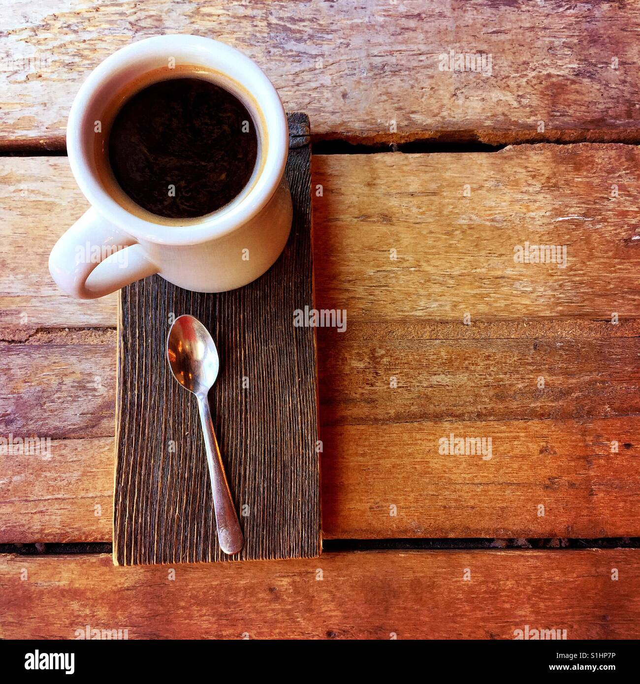 An overhead shot of a fresh Americano beverage and a spoon on a wood serving plate on a wooden table - Stock Image