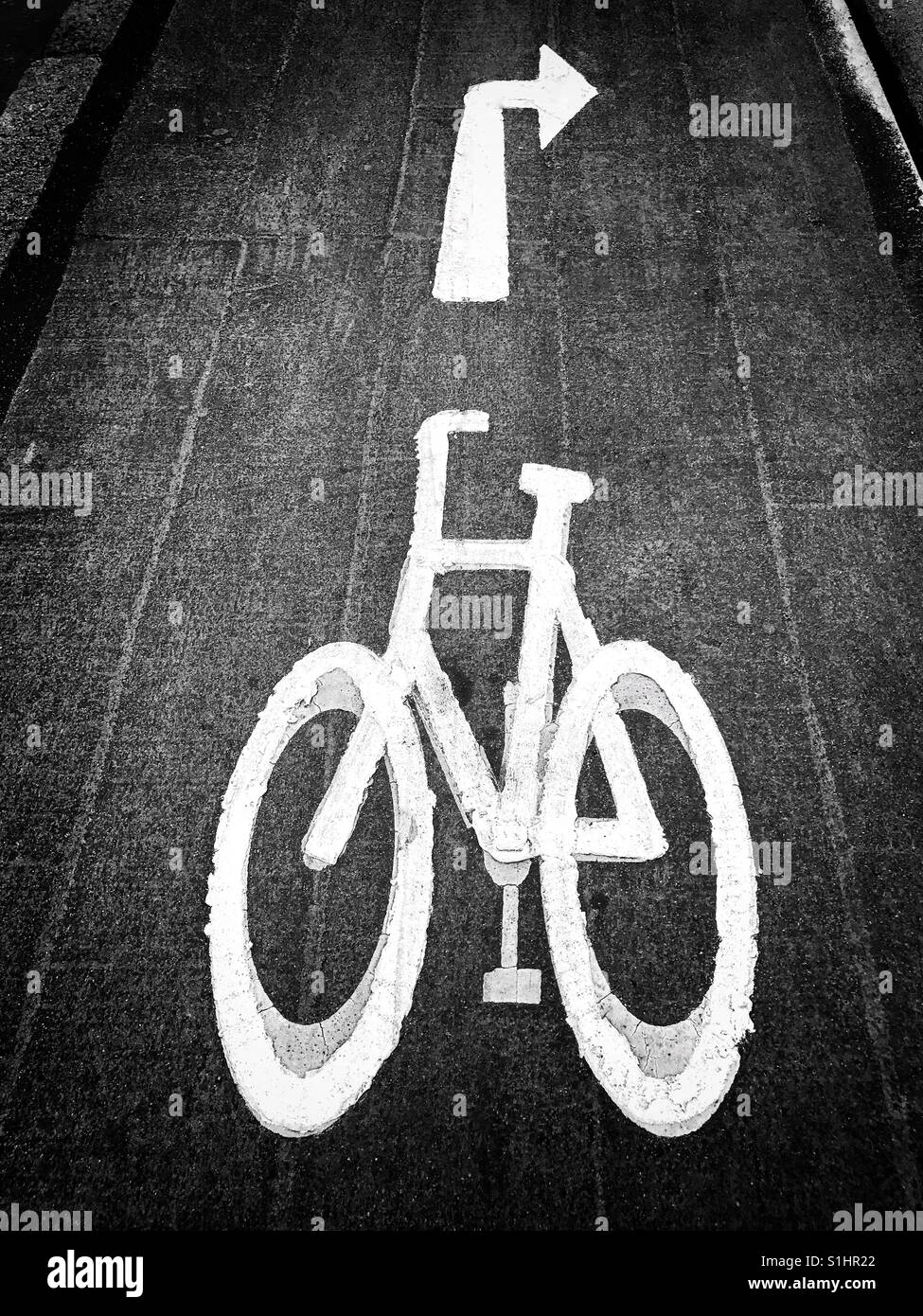 A painted white symbol of a bicycle in an urban area - this is a dedicated cycle lane. The arrow indicates cyclists - Stock Image