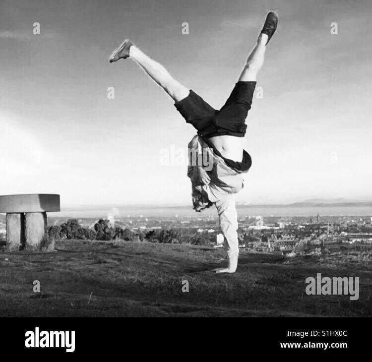 One handed cartwheel on the top of braid hill in Edinburgh, Scotland. - Stock Image