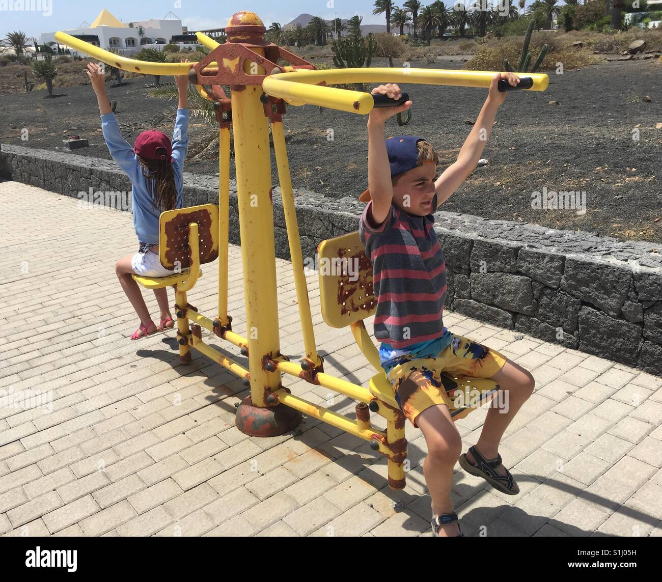 Boy and girl working out in the sun - Stock Image
