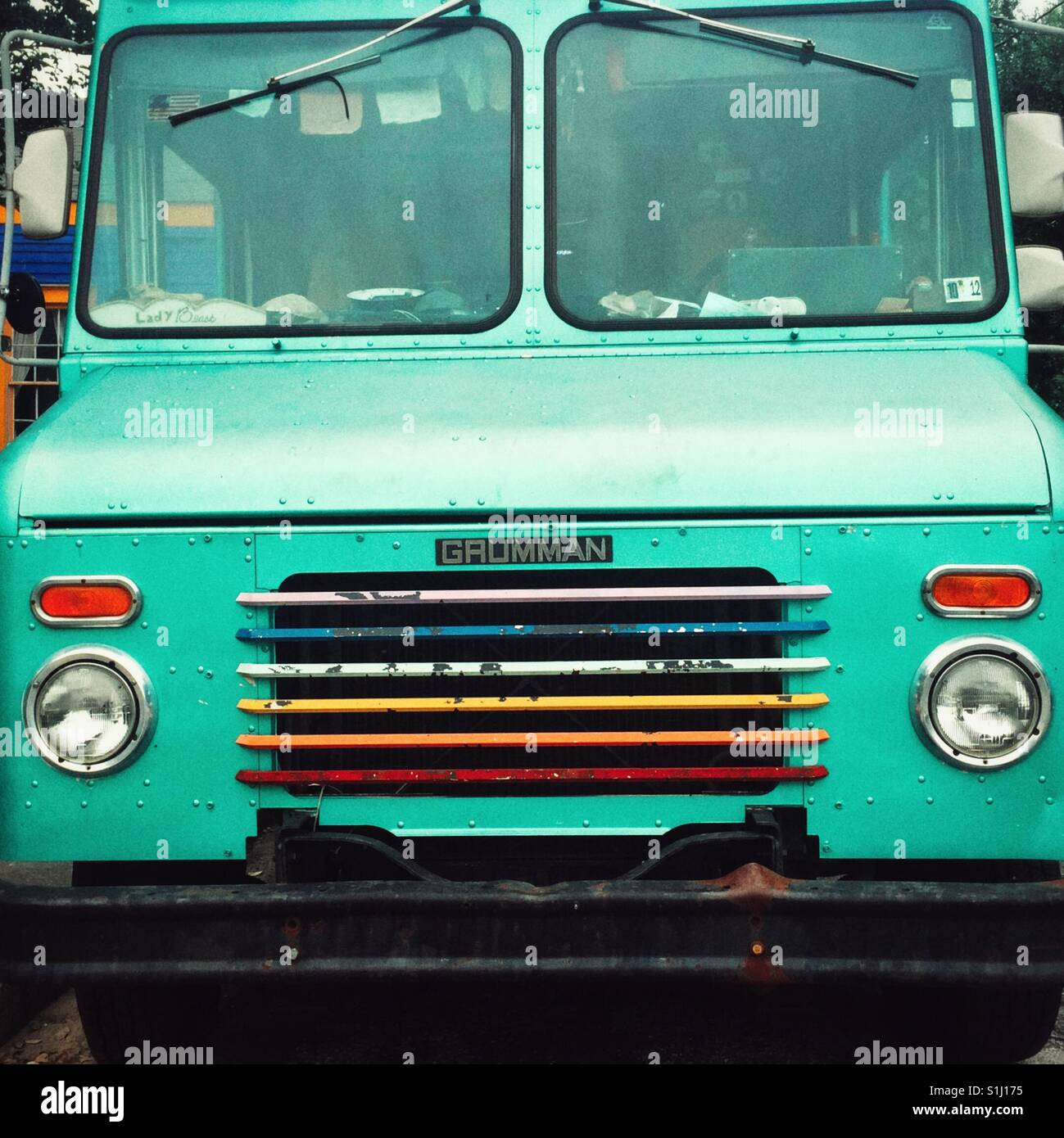 Turquoise colored truck with rainbow painted grill in front on the street in New Orleans - Stock Image