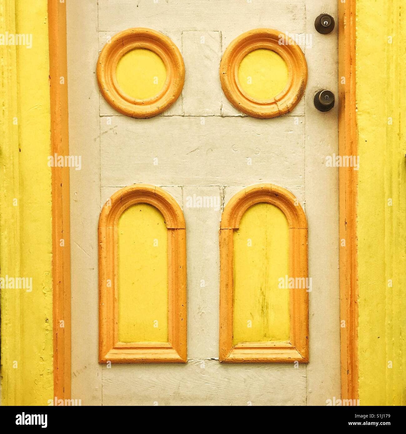 Decorative elements on the door in New Orleans painted bright yellow - Stock Image