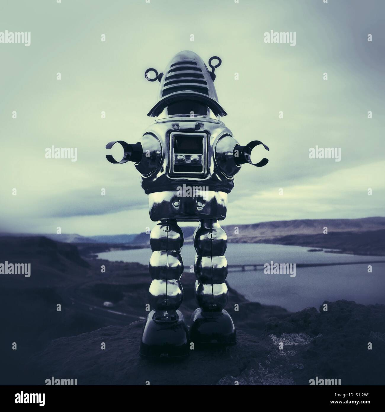 Vintage metal toy robot standing on high bank of Columbia river in Eastern Washington - Stock Image