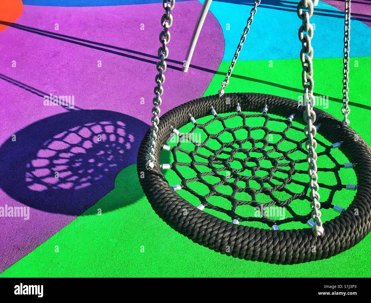 A children's swing hangs silently in a new & colourful playground area. It's a summer's afternoon - Stock Image